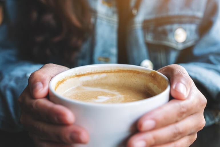 Kaffee Latte in der Hand